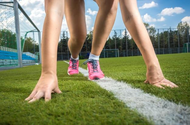 Strzał zbliżenie szczupła sportowa kobieta przygotowuje się do biegu na torze trawy