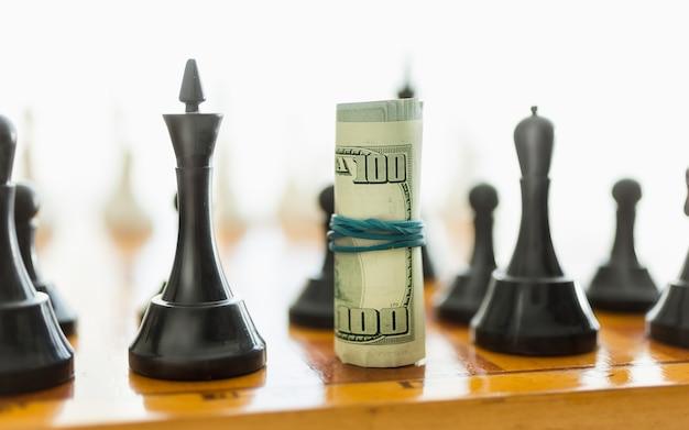 Strzał zbliżenie walcowanych dolarów na miejsce o czarny kawałek szachowy