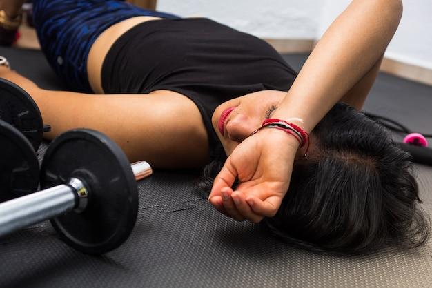 Strzał zbliżenie wyczerpanej kobiety leżącej na podłodze po ćwiczeniach i treningu