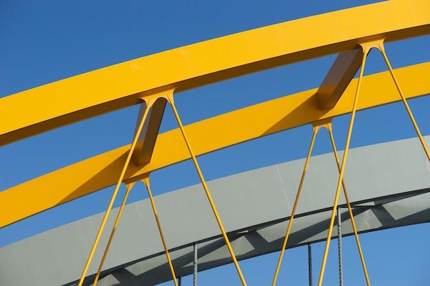 Strzał zbliżenie żółty metalowy łuk pod błękitnym niebem