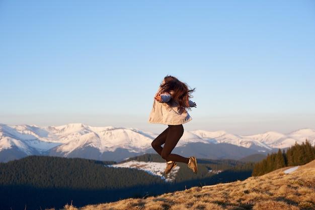 Strzał żeński wycieczkowicz skacze w powietrzu na górze góry