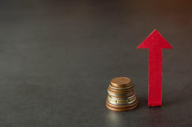 Strzała i pieniądze odizolowywający na zmroku. zarabiaj, zwiększaj lub podwyższaj swoje pieniądze. finanse i biznes. copyspace.