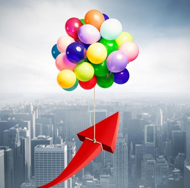Strzałka podniesiona przez latające balony. latać do sukcesu gospodarczego