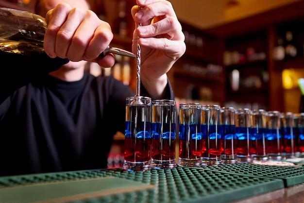 Strzały alkoholowe na ladzie barowej. profesjonalny barman nalewa alkoholowe strzały.