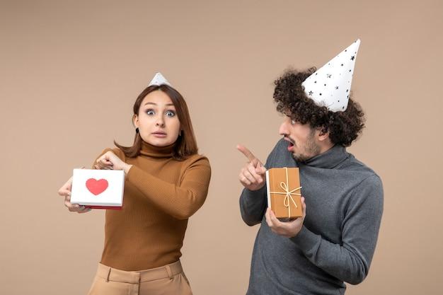 Strzelanie noworoczne z emocjonalną, szaloną, zdezorientowaną młodą parą nosić kapelusz noworoczny dziewczyna z sercem