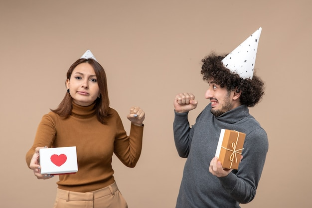 Strzelanie noworoczne z emocjonalną, szaloną zszokowaną młodą parą nosi noworoczną dziewczynę z sercem
