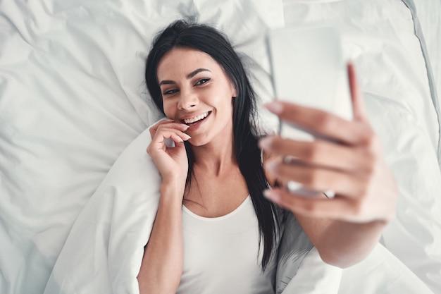 Strzelanie online. niesamowita długowłosa kobieta demonstruje swój przyjazny uśmiech podczas komunikacji online ze swoją przyjaciółką