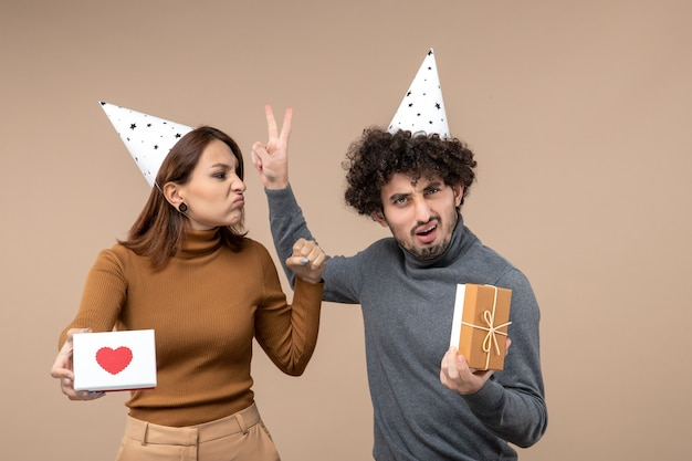 Strzelanina noworoczna z emocjonalną, zszokowaną, zszokowaną młodą parą nosi kapelusz noworoczny zły dziewczyna