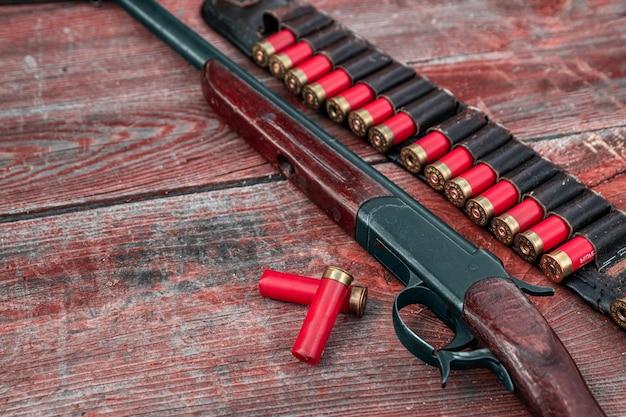 Strzelba i naboje pod patronatem leżą na drewnianym stole