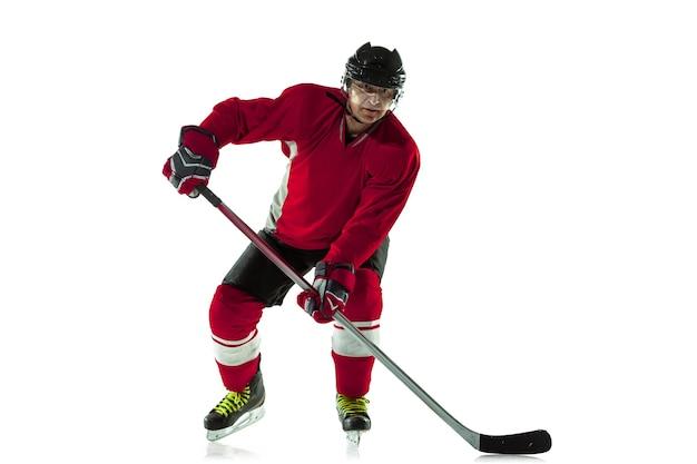 Strzeleniu gola. męski gracz w hokeja z kijem na boisku i białej ścianie. sportowiec noszący sprzęt i kask ćwiczący. pojęcie sportu, zdrowego stylu życia, ruchu, ruchu, działania.