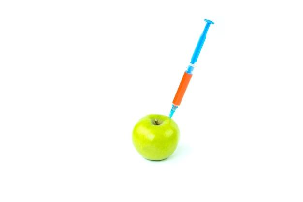 Strzykawka i jabłko na białym tle