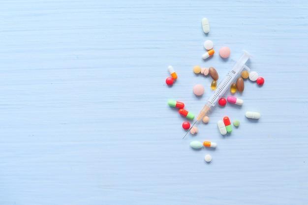 Strzykawka i tabletki na białej przestrzeni, widok z góry