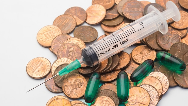 Strzykawka i zielony lek na kapsułkę na stosie monet 1 centa, symbol kosztów opieki zdrowotnej