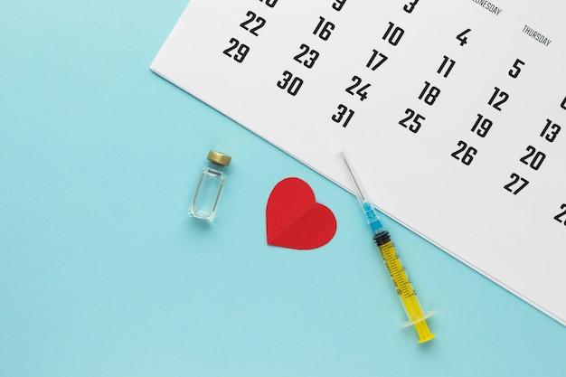 Strzykawka, szklana fiolka z płynem, kalendarz i czerwone papierowe serce na niebieskim tle.