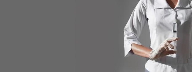 Strzykawka z ostrą igłą w rękach lekarzy lub pielęgniarek na szarym sztandarze z miejscem na tekst