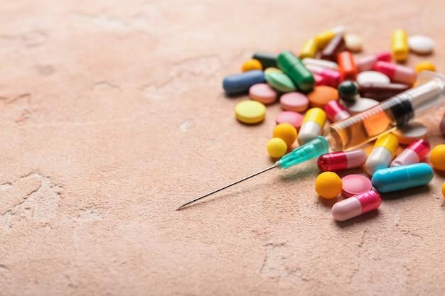 Strzykawka z pigułkami na kolorowej powierzchni