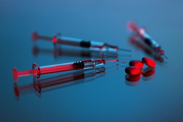 Strzykawki i tabletkimedycyna na niebieskim tle, szczepionka i lek na wirusa covid19 korona