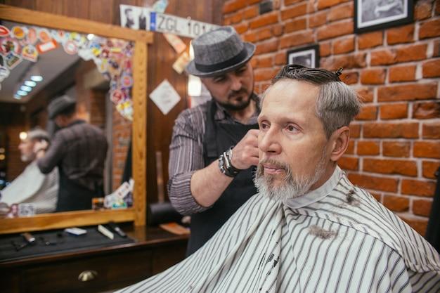 Strzyżenie dziadka u fryzjera w sklepie fryzjerskim
