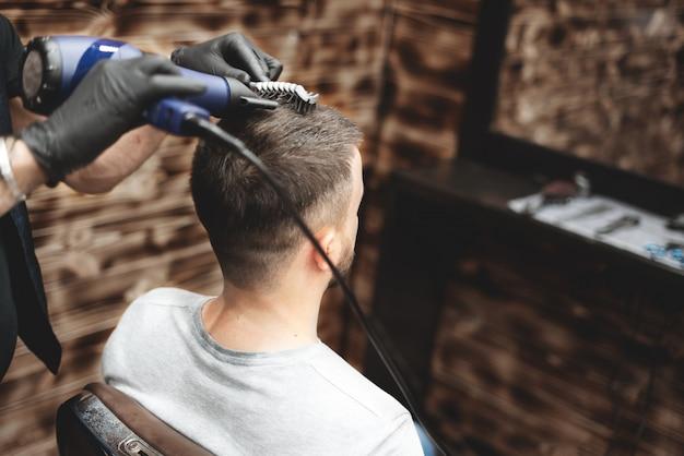 Strzyżenie głowy w zakładzie fryzjerskim. fryzjer ścina włosy na głowie klienta. proces tworzenia fryzur dla mężczyzn. fryzjer. selektywne ustawianie ostrości.
