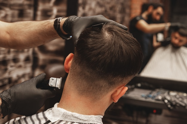 Strzyżenie głowy w zakładzie fryzjerskim. fryzjer ścina włosy na głowie klienta. proces tworzenia fryzur dla mężczyzn. fryzjer