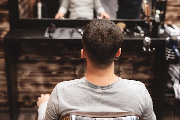 Strzyżenie głowy w zakładzie fryzjerskim. fryzjer ścina włosy na głowie klienta. proces tworzenia fryzur dla mężczyzn. fryzjer.