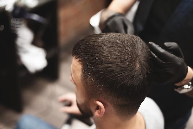 Strzyżenie głowy w zakładzie fryzjerskim. fryzjer ścina włosy na głowie klienta. proces tworzenia fryzur dla mężczyzn.