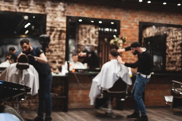 Strzyżenie głowy w zakładzie fryzjerskim, fryzjer ścina włosy na głowie klienta.