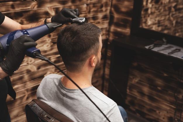Strzyżenie głowy w zakładzie fryzjerskim. fryzjer ścina włosy na głowie klienta
