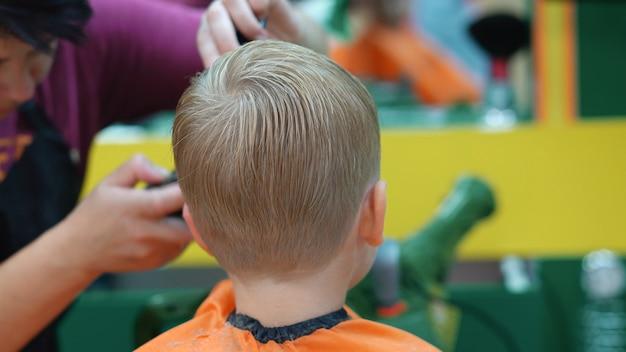 Strzyżenie małego chłopca w salonie fryzjerskim dla dzieci