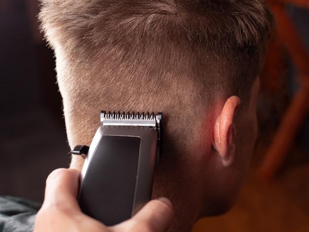 Strzyżenie męskie, mistrz wycina młodego faceta z bliska maszynką do strzyżenia włosów, narzędzie fryzjerskie.