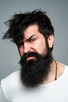 Strzyżenie męskie, nowoczesne fryzury. bliska portret model mężczyzna z długimi włosami. koncepcja opieki zdrowotnej i pielęgnacji włosów. brodaty hipster.