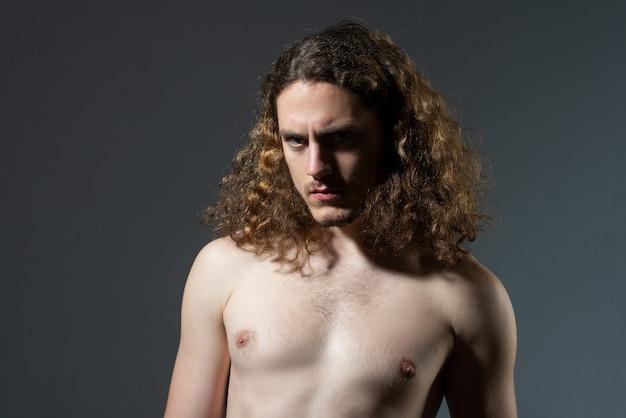 Strzyżenie męskie, nowoczesne fryzury. bliska portret seksowny model mężczyzna z długimi kręconymi włosami. koncepcja opieki zdrowotnej i pielęgnacji włosów.