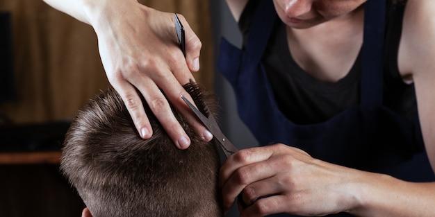 Strzyżenie męskie nożyczkami w domu. fryzjer działa w domu.