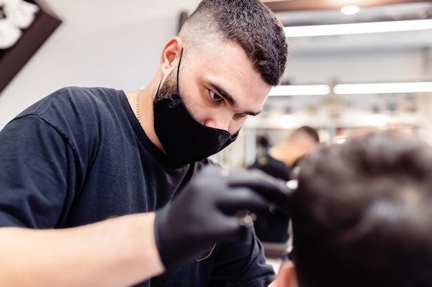 Strzyżenie męskie w salonie fryzjerskim. klient i fryzjer w maskach antywirusowych. strzyżenie w kwarantannie.