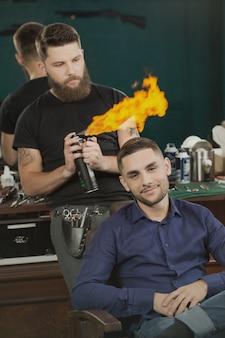 Strzyżenie ognia przystojny mężczyzna uśmiecha się, siedząc w fotelu fryzjerskim, podczas gdy jego brodaty fryzjer rozpylania ognia płonie z lakierem do włosów za nim