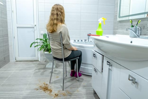 Strzyżenie w salonie w domu podczas kwarantanny. dziewczyna z długimi włosami siedzi na krześle w łazience, włosy obcięte na podłodze wokół niej. zamknięte salony kosmetyczne z powodu pandemii. domowa rozrywka, wypoczynek.