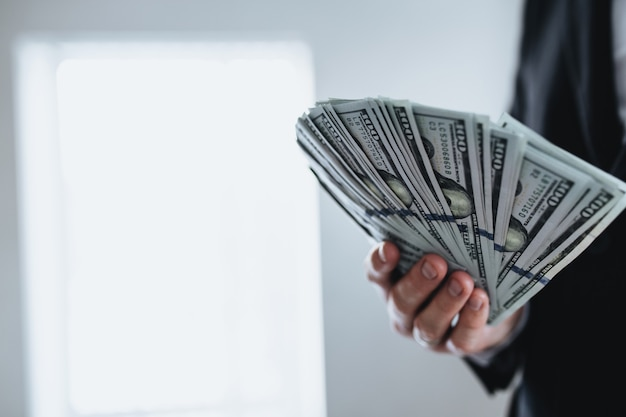 Stu dolarowe pieniądze zabawa, w ręku mężczyzna w garniturze i białej koszuli. niewyraźne tło. wysokiej jakości zdjęcie