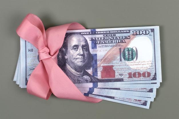 Stu dolarowy związany z różową kokardą na szaro