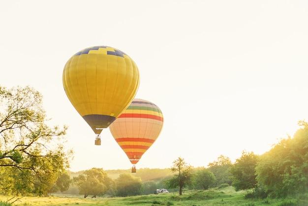 Stubarwni gorące powietrze balony lata nad dolina w niebie przy rankiem. balon w naturze.