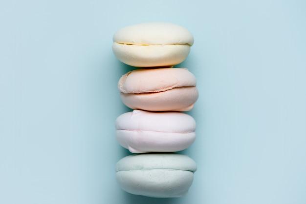 Stubarwny marshmallow na błękitnym tle. kolorowe słodycze. pyszny zefir.