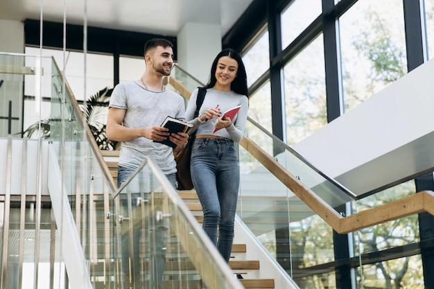 Studenci chodzą po schodach z książkami w bibliotece