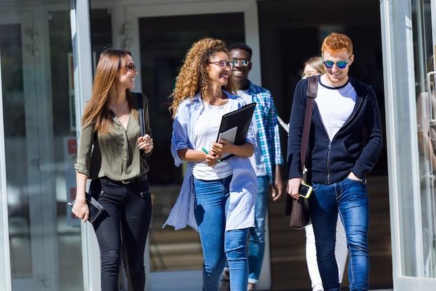 Studenci chodzą w hali uniwersyteckiej podczas przerwy i komunikują się.