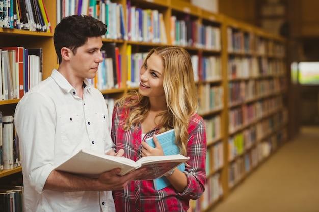 Studenci collegu czyta książkę wpólnie w bibliotece
