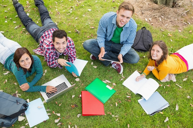 Studenci collegu używa laptop podczas gdy robić pracie domowej w parku