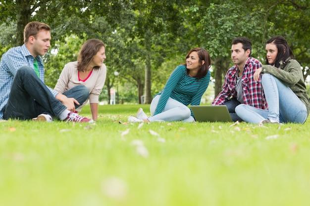 Studenci collegu z laptopu obsiadaniem w parku
