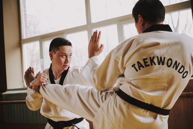 Studenci ćwiczą sztuki walki na siłowni.