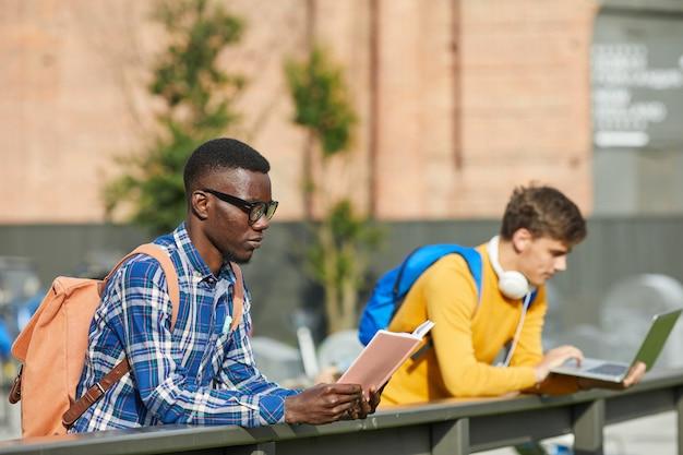 Studenci czytający na zewnątrz