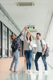 Studenci dający wysokie piątki w hali