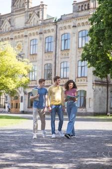 Studenci. dwóch chłopaków i dziewczyna chodzą i dyskutują o przyszłych egzaminach