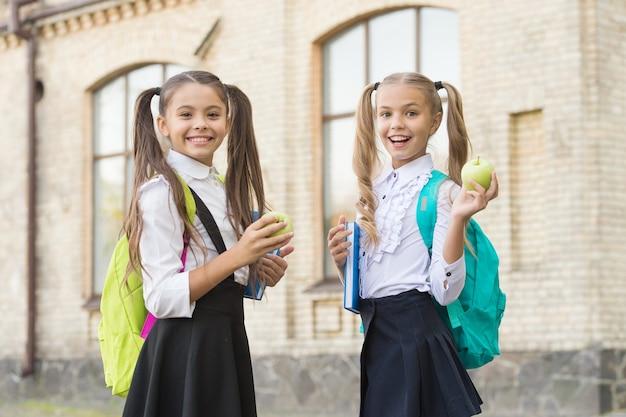 Studenci dziewczyny z klasy z plecakami po szkolnym lunchu, koncepcja żywności na śniadanie.